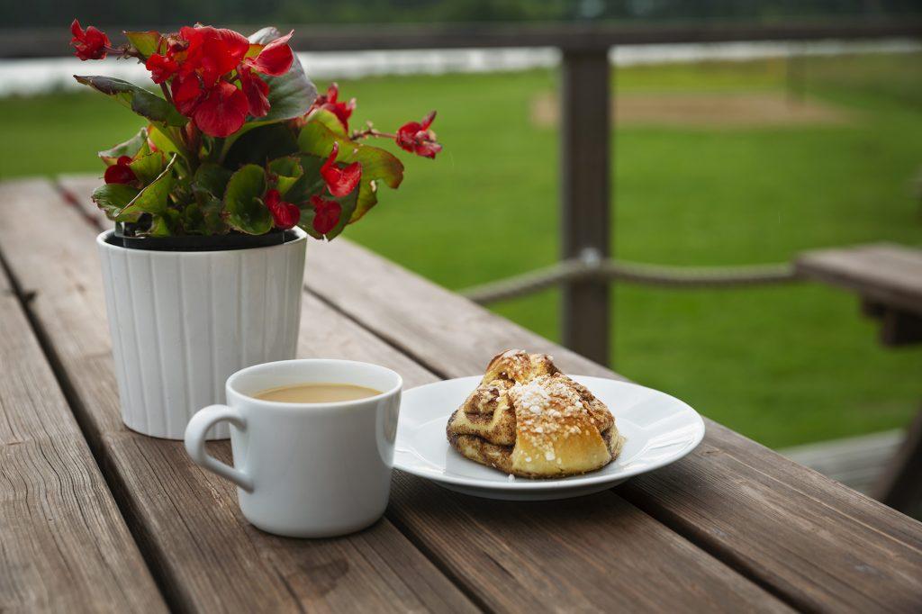 Kesäkahvila Jokiranta, terassipöydällä kahvikuppi, korvapuusti lautasella ja kukka.