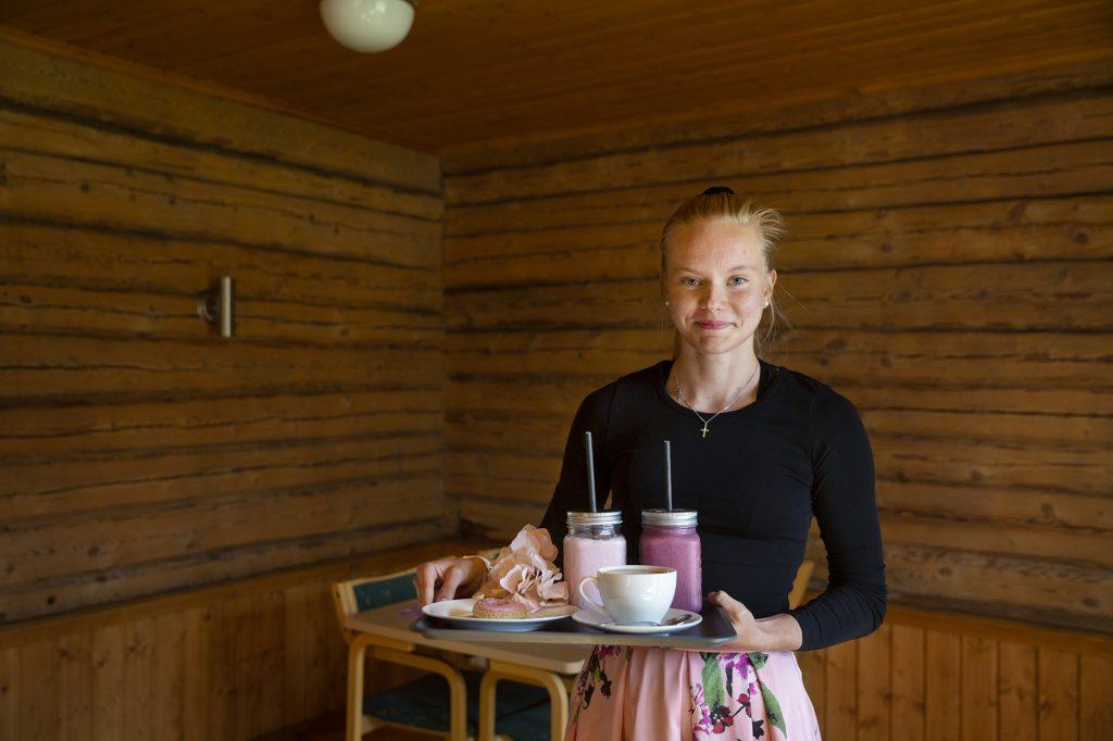 Kesäkahvila Vellikello, nuori nainen täyden tarjottimen kanssa.