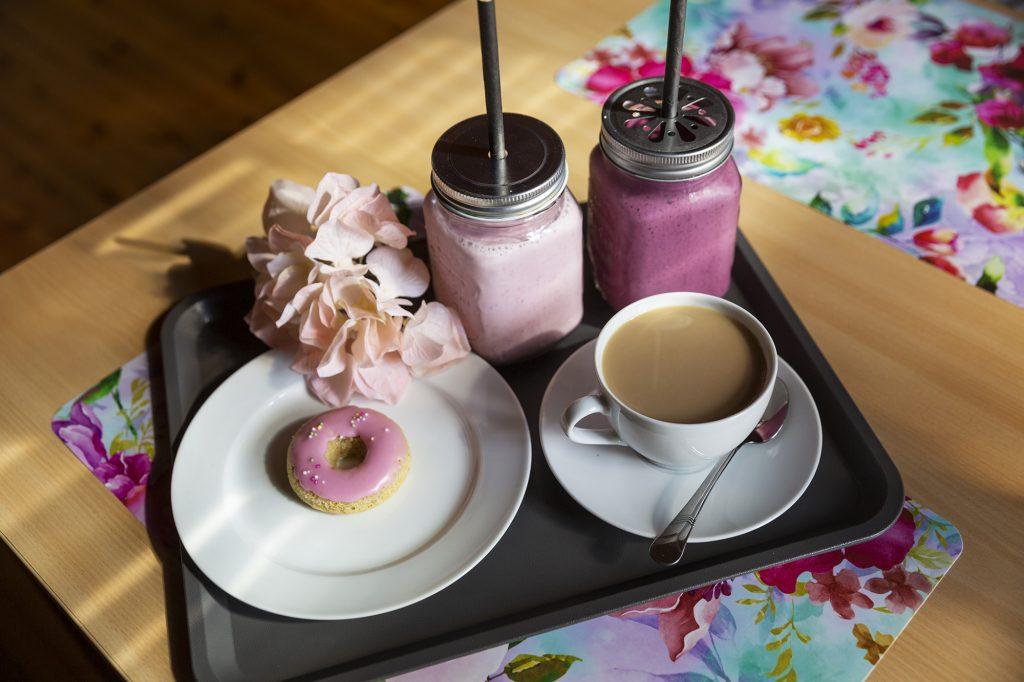 Kesäkahvila Vellikello, pöydällä olevalla tarjottimella kahvikuppi, donitsi ja kaksi smoothieta.