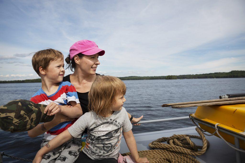 Äiti ja kaksi lastan veneen kannella kesällä.
