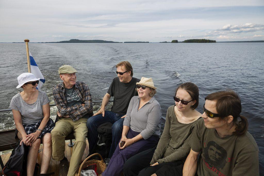 Ihmisiä istumassa aluksen kannella pilvisenä kesäpäivänä, takana näkyy Höytiäisen vesistöä.