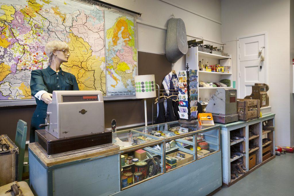 Wanhan mestan museo, vanhan ajan kauppatiski ja tarvikkeita, kassaneitinä naispuolinen mallinukke