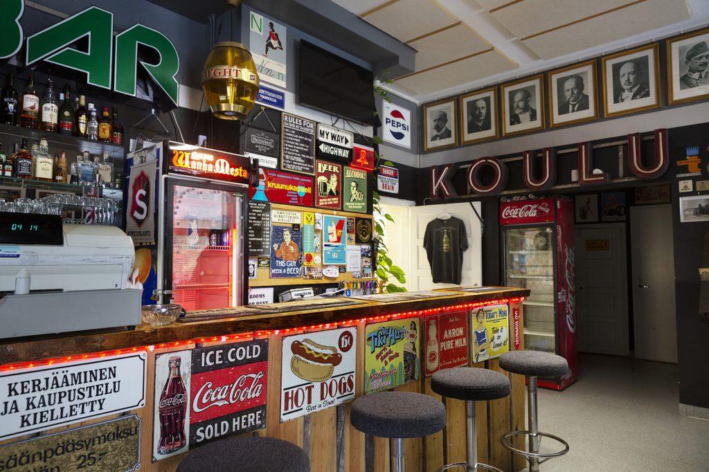 Wanhan mestan museo, baaritiski, joka sisustettu vanhoilla mainoskylteillä ja julisteilla.