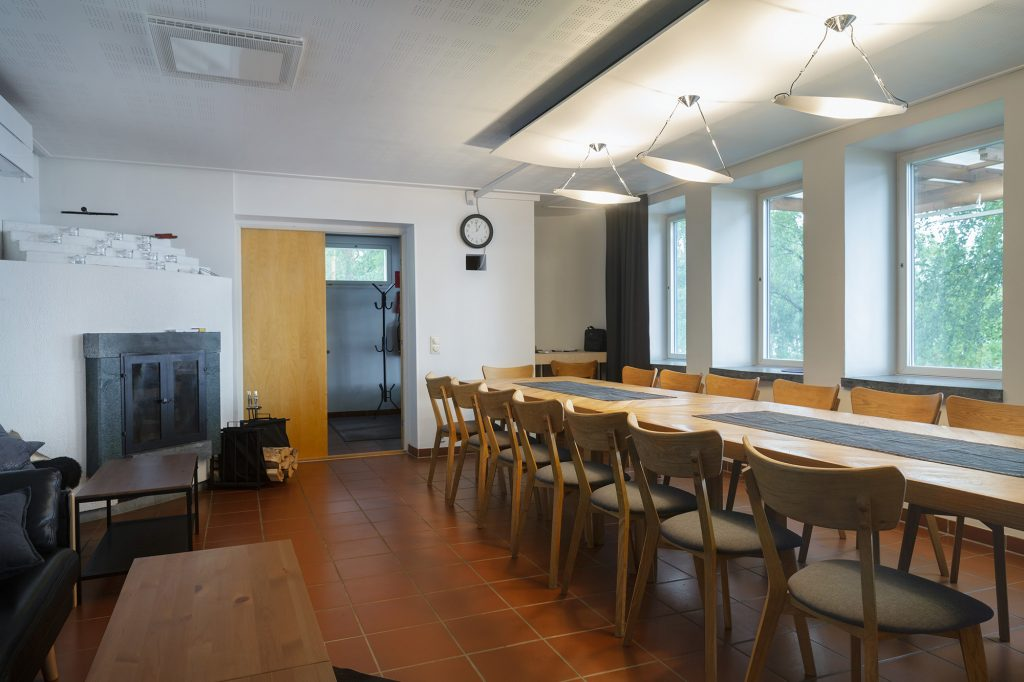 Juhlatila Lautsan sali, jossa takka ja pitkä pöytä tuoleineen.