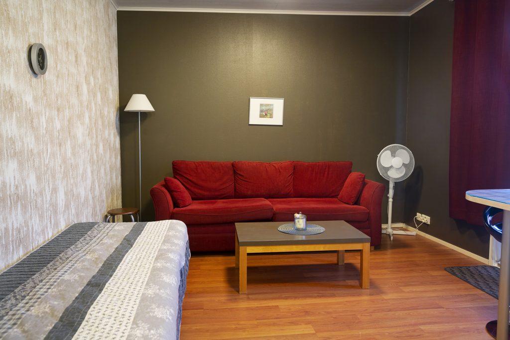 Motelli Kontio, sohva ja sänky majoitushuoneessa.