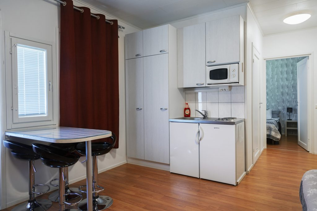 Motelli Kontio, pienoiskeittiö ja ruokapöytä majoitushuoneessa.
