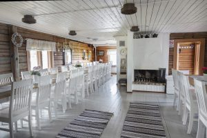 Höytiäisen Helmen sali, jossa pitkät ruokapöydät ja avotakka.