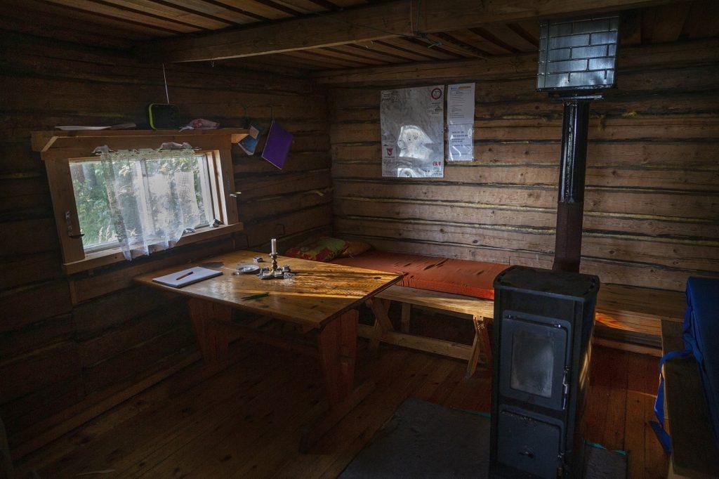 Vanha hirsiseinäinen kalamaja sisältä, pirtinpöytä, laveri ja kamiina.