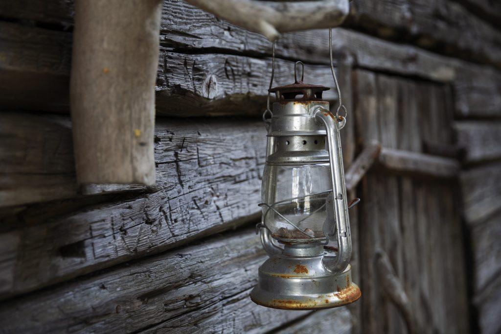 Lyhty roikkumassa vanhan harmaan kalamajan seinustalla.