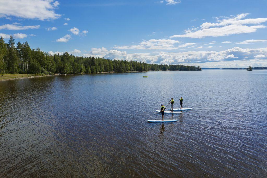 Sup-lautailijoita kesäisessä järvimaisemassa.