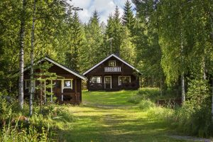 Pohjan tilan Hirsituvat, hirsimökki ja saunarakennus kesällä.