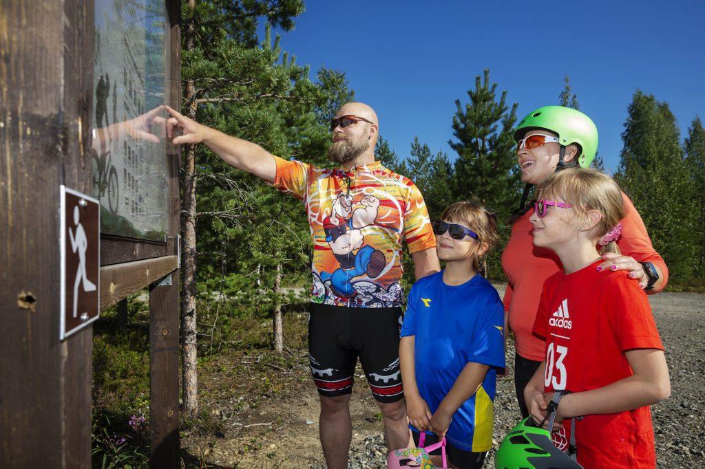 Nelihenkinen perhe opastaulun ääressä lähdössä maastopyöräilemään.