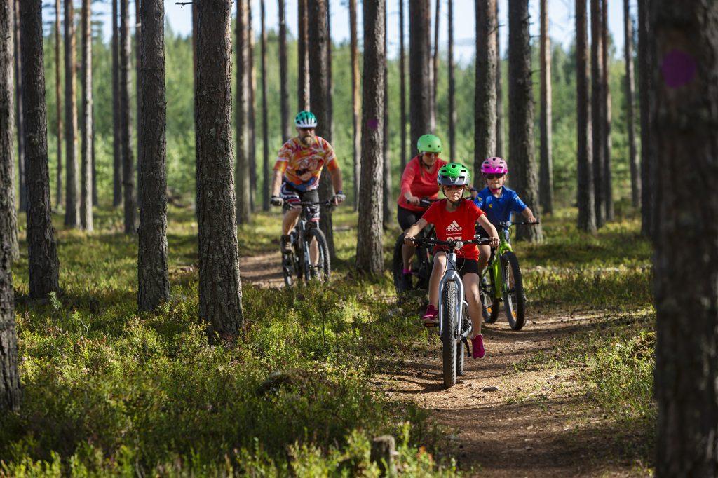Nelihenkinen perhe maastopyöräretkellä kesällä.