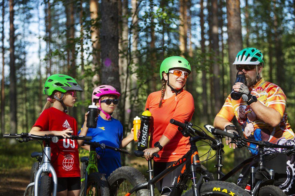 Nelihenkinen perhe juomatauolla maastopyöräretkellä kesällä.