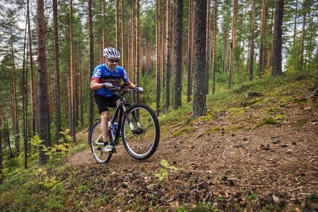 Mies maastopyöräilee jyrkkää rinnettä ylös.