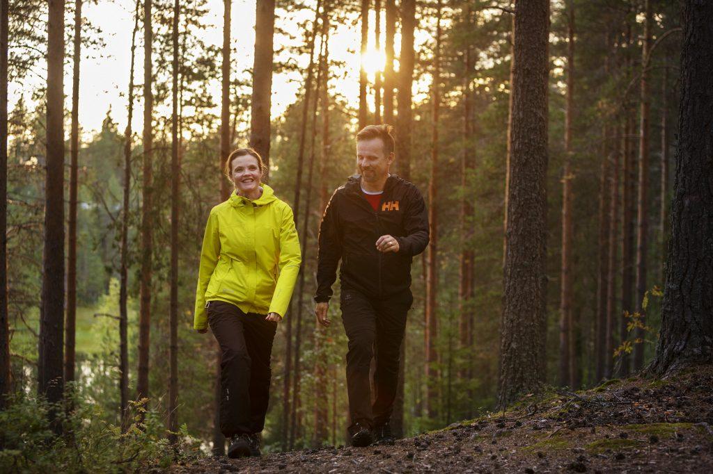 Pariskunta kävevee metsässä ilta-auringossa.