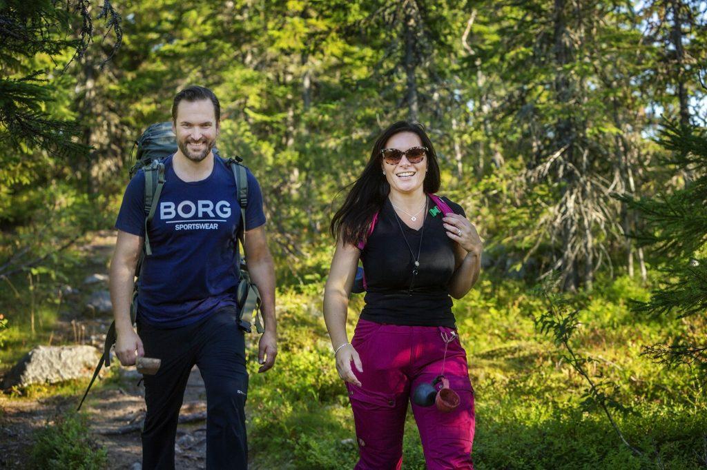 Iloinen pariskunta patikoimassa metsässä reput selässä.