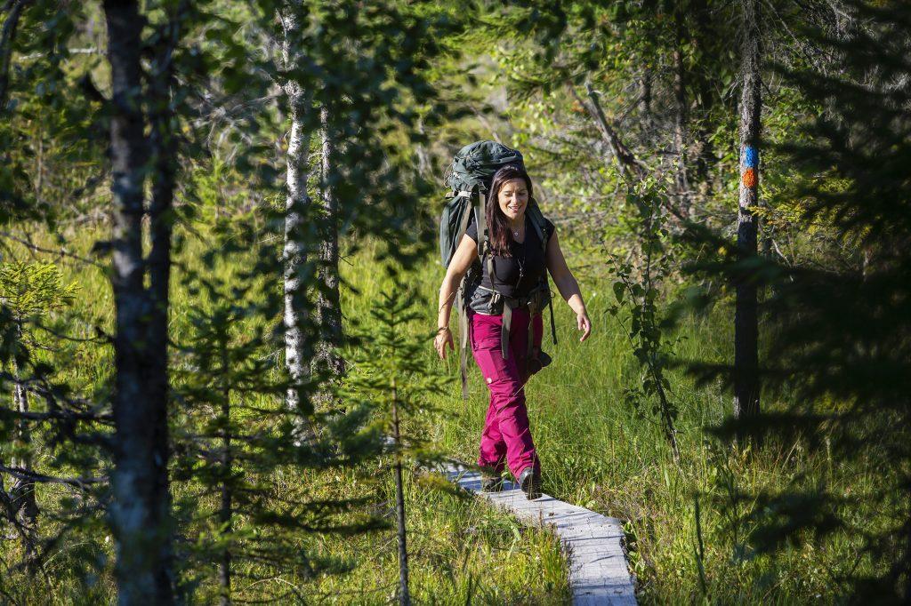 Nainen kävelee rinkka selässä pitkospuita pitkin.