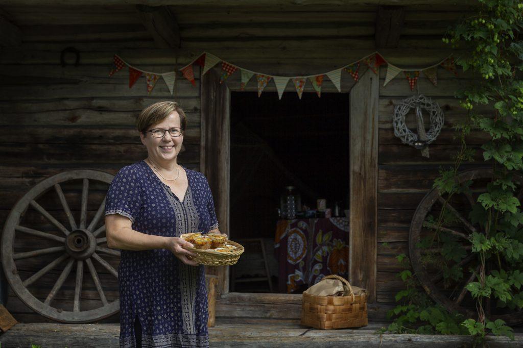 Alapihan Arboretum, nainen hymyilee tarjoiluvati käsissä vanhan aitan edessä.