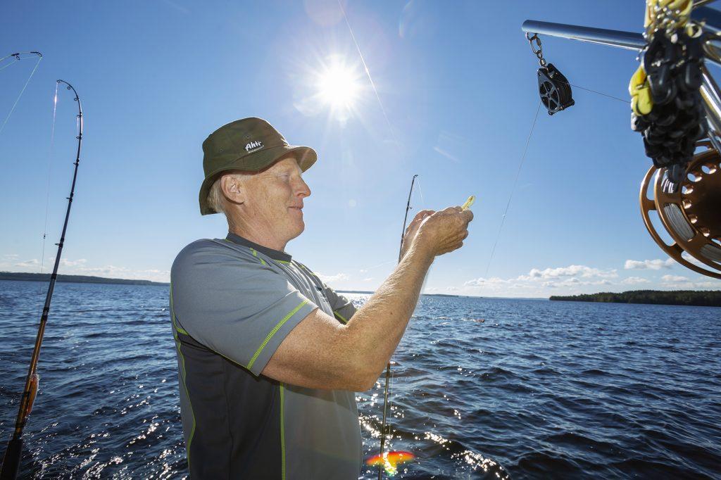 Mies valmistelee uisteluvapaa kalastusta varten veneessä aurinkoisena kesäpäivänä Höytiäisellä.