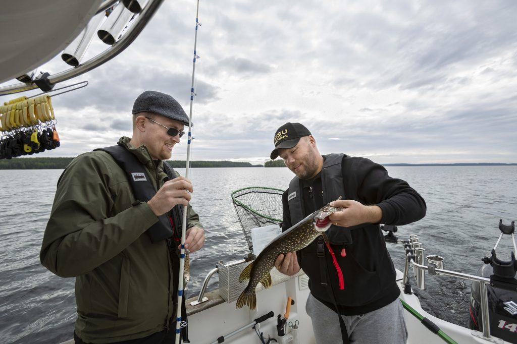Kaksi miestä kalastusveneessä järvellä, toisella hauki käsissään.
