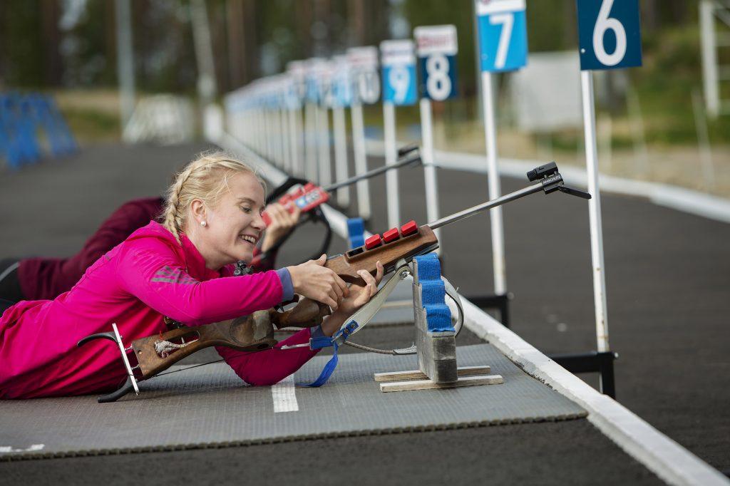 Nainen säätää asetta makuuasennossa ampumahiihtostadionilla.