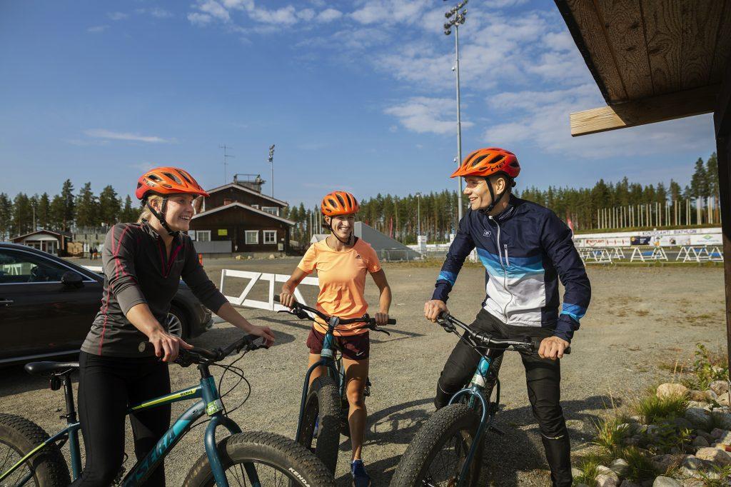 Kolme nuorta aikuista maatopyörien kanssa opastaulun luona.