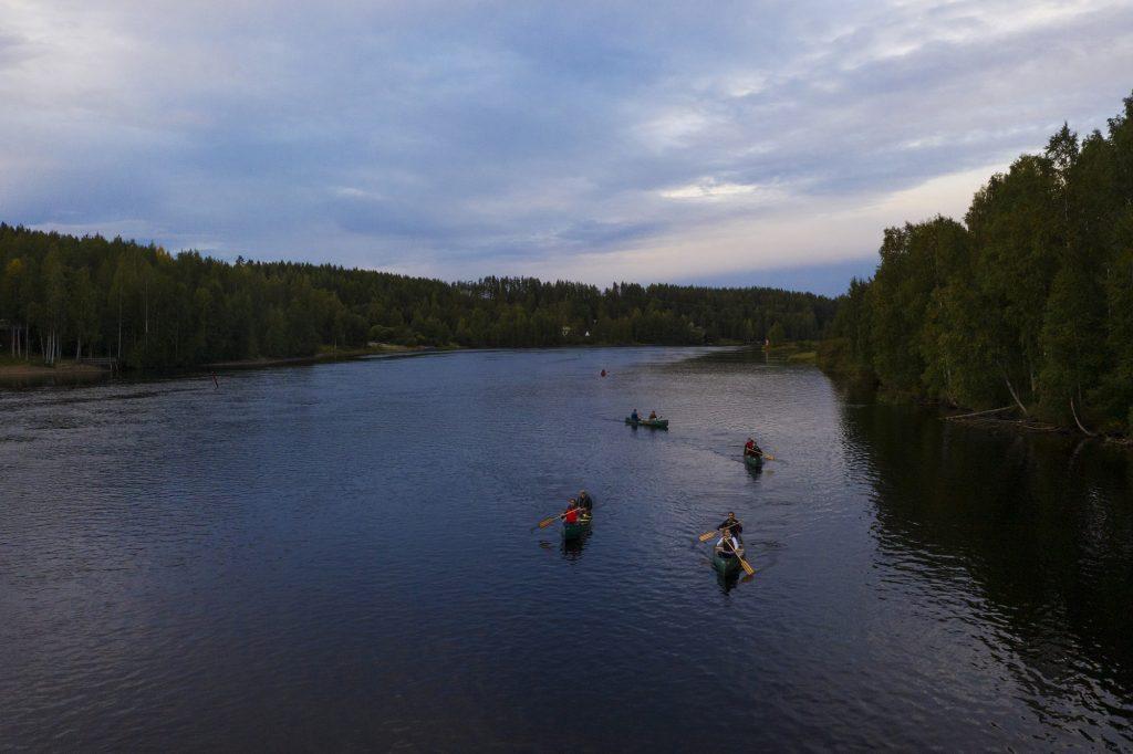 Useita melojia intiaanikanooteilla joella kesäiltana ylhäältä viistosti kuvattuna.