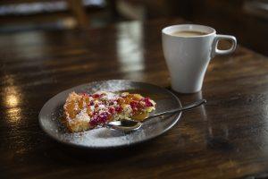 Kupillinen kahvia ja pala marjapiirakkaa lautasella.