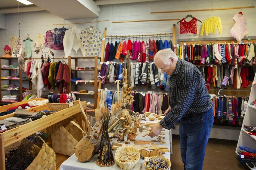 Käsityömyymälä Tiuhta, vanhempi mies järjestelee puisia käsitöitä, takana myytäviä villasukkia ja muista käsitöitä.