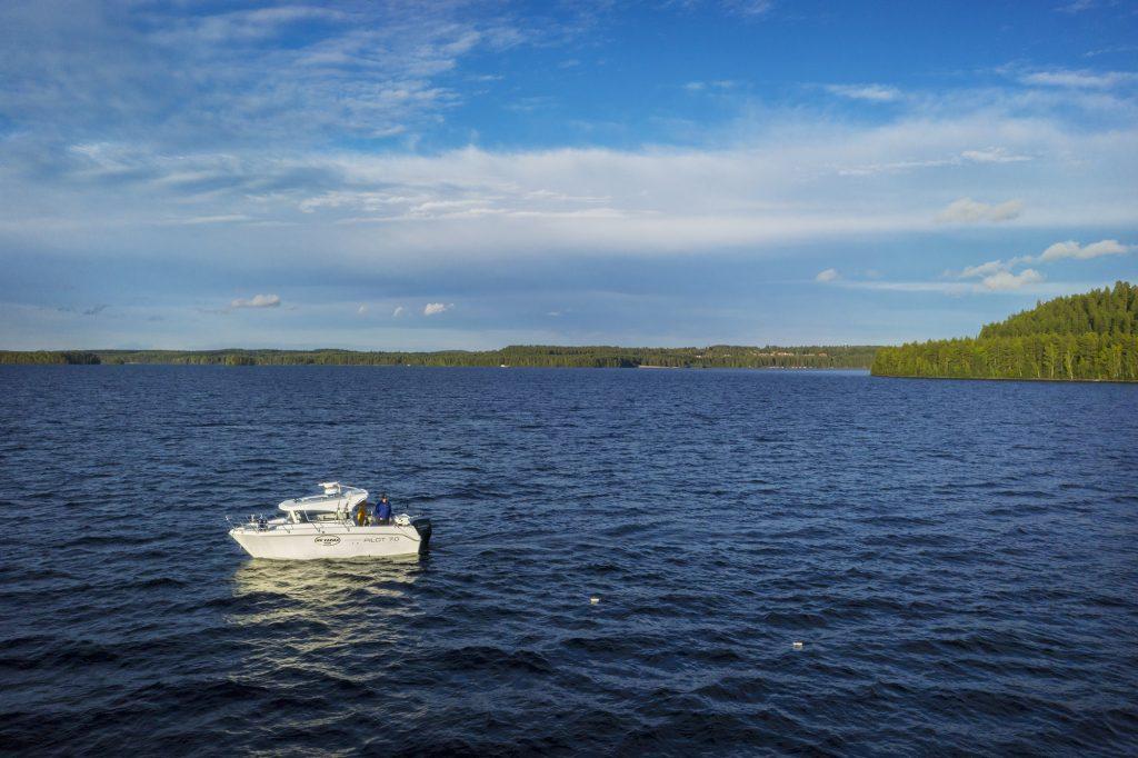 Uisteluvenee uistelee aurinkoisella Höytiäisellä, ylhäältä viistosta kuvattu.