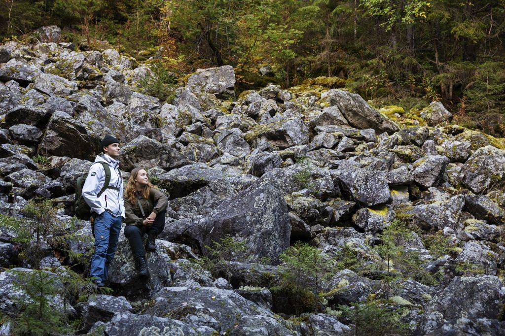 Nuori nainen ja mies katselevat maisemaa kivisessä louhikossa Kolvananuuron rotkolaaksossa Kontiolahdella.
