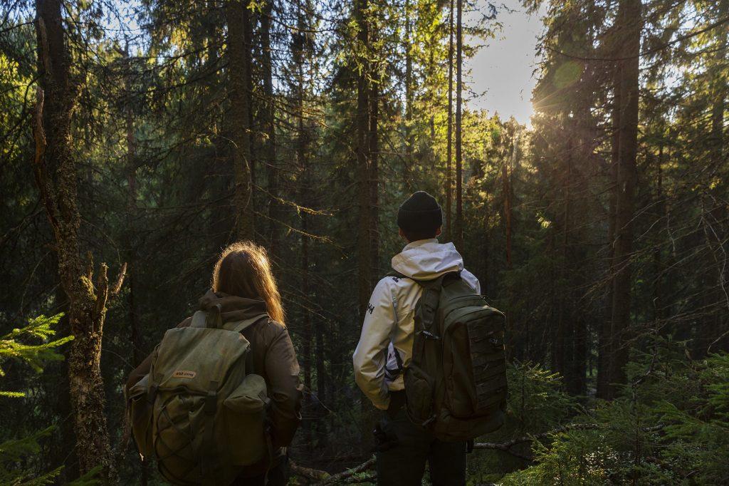 Nuori mies ja nainen katsovat metsämaisemaa selin kameraan.