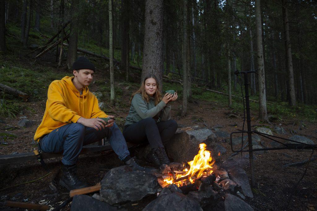 Nuori nainen ja mies istuvat hämärässä nuotiolla ja juovat kupeista.