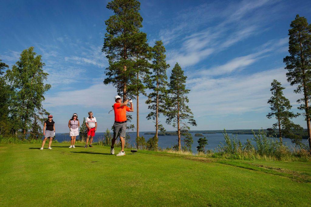 Neljä golfaajaa Karelia Golfin nurmella, takana siintää kesäinen Höytiäinen.